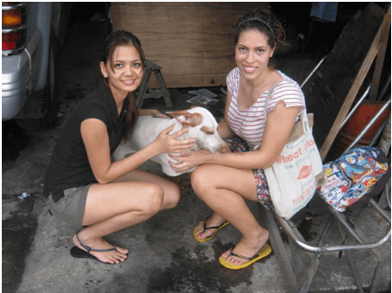 Esmee Joseph and fellow intern Charm Murray pose with Christmas while volunteering for Pasay Pups.