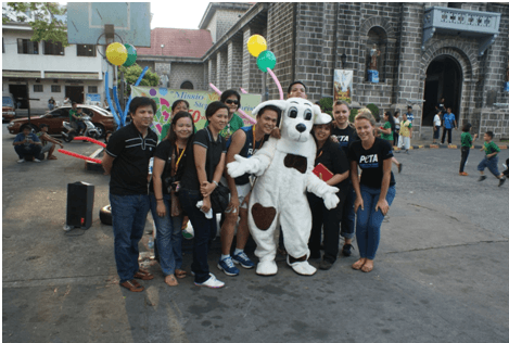 """Milena König (far right), Spot the """"dog,"""" and others pose at a tabling event in Manila."""